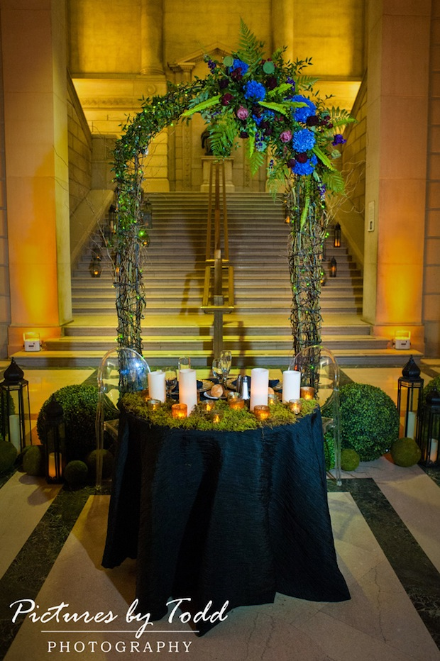 Beautiful Blooms Sweetheart Table Arch Ghost Chairs Candles Lanterns Boxwood Enchanted Garden Moss Blue Purple Burgundy Flowers Pictures by Todd Free Library of Philadelphia Greenery